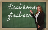 Teacher showing First come, first served on blackboard — Stock Photo