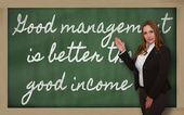 Teacher showing Good management is better than good income on bl — Stock Photo