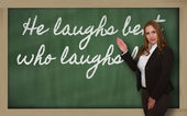 Teacher showing He laughs best who laughs last on blackboard — Stockfoto