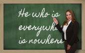 Teacher showing He who is everywhere is nowhere on blackboard — Zdjęcie stockowe