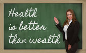 Teacher showing Health is better than wealth on blackboard — Stockfoto