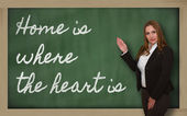 Teacher showing Home is where the heart is on blackboard — Stock Photo
