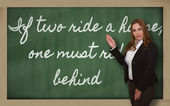 Teacher showing If two ride a horse, one must ride behind on bla — Stockfoto