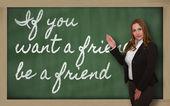 Teacher showing If you want a friend, be a friend on blackboard — Stockfoto