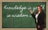 Teacher showing Knowledge in youth is wisdom in age on blackboar — Stock Photo