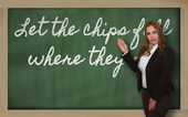 Teacher showing Let the chips fall where they may on blackboard — Stock Photo