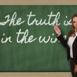Teacher showing The truth is in the wine on blackboard — Stock Photo