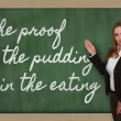 Teacher showing The proof of the pudding is in the eating on bla — Foto de Stock