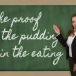 图库照片: Teacher showing proof of pudding is in eating on bla