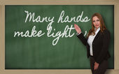 Teacher showing Many hands make light work on blackboard — Foto de Stock
