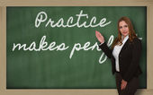 Teacher showing Practice makes perfect on blackboard — Stock Photo