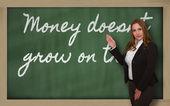 Teacher showing Money doesn t grow on trees on blackboard — Stock Photo