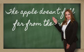 Teacher showing The apple doesn t fall far from the tree on blac — Stockfoto