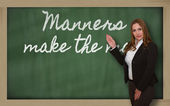 Teacher showing Manners make the man on blackboard — Stock Photo
