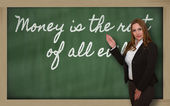 Teacher showing Money is the root of all evil on blackboard — Foto Stock