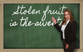 Teacher showing Stolen fruit is the sweetest on blackboard — Stock Photo