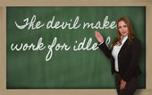 Teacher showing The devil makes work for idle hands on blackboar — Zdjęcie stockowe