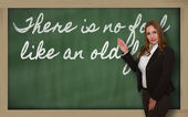 Teacher showing There is no fool like an old fool on blackboard — Photo