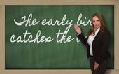 Teacher showing The early bird catches the worm on blackboard — Stock Photo