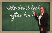 Teacher showing The devil looks after his own on blackboard — Stock fotografie