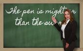 Teacher showing The pen is mightier than the sword on blackboard — Stock Photo
