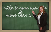 Teacher showing The tongue wounds more than a lance on blackboar — Stock Photo