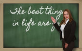 Teacher showing The best things in life are free on blackboard — Stock Photo