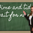 Teacher showing Time and tide wait for no man on blackboard — Stock Photo