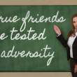 Teacher showing True friends are tested in adversity on blackboa — Stock Photo #26042129