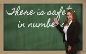 Teacher showing There is safety in numbers on blackboard — Stock Photo