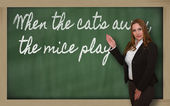 Teacher showing When the cat s away, the mice play on blackboard — Stock Photo