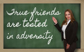 Teacher showing True friends are tested in adversity on blackboa — Zdjęcie stockowe