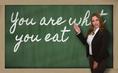 Teacher showing You are what you eat on blackboard — Stockfoto