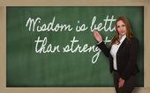 Teacher showing Wisdom is better than strength on blackboard — Stock Photo