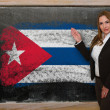 Teacher showing flag ofCuba on blackboard for presentation marke — Stock Photo