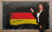Teacher showing flag ofGermany on blackboard for presentation ma — Stock Photo
