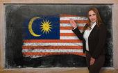 Teacher showing flag ofMalaysia on blackboard for presentation m — Stock Photo