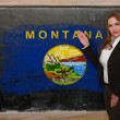 Teacher showing flag ofmontana on blackboard for presentation ma - Stock Photo
