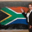 Teacher showing flag ofSouth Africa on blackboard for presentati — Stock Photo