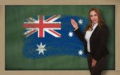 Teacher showing flag ofaustralia on blackboard for presentation — Stock Photo