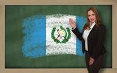 Teacher showing flag ofguatemala on blackboard for presentation — Stock Photo
