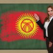 Teacher showing flag ofkirghizstan on blackboard for presentatio — Stock Photo