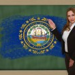 Teacher showing flag of new hampshire on blackboard for presentat — Stock Photo #26245025