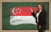 учитель показывает флаг ofsingapore на доске для презентации — Стоковое фото