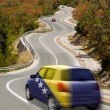 Car on road in national flag of bosnia herzegovina colors — Stock Photo