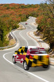 Car on road in flag of american state of maryland colors — Stock Photo