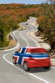 Car on road in national flag of norway colors — Stock Photo