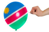 Bursting balloon colored in national flag of namibia — Stock Photo