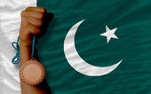 Bronze medal for sport and national flag of pakistan — Stock Photo