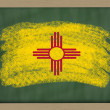Flag of us state of new mexico on blackboard painted with chalk — Stock Photo #8840190
